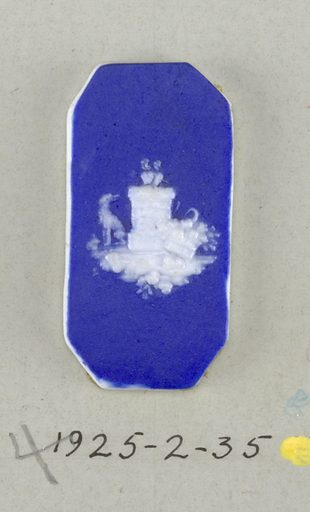 Octagonal mount in the style of Wedgwood Jasperware; ornamented with pierced heart on a pedestal with a dog and a basket of flowers at its base; white on blue ground. Date: 1800s. Record ID: chndm_1925-2-35.