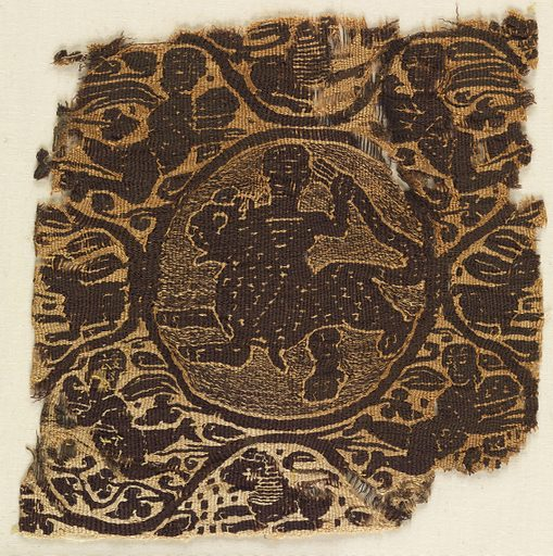Fragment of a tapestry-woven square. Monochrome type, dark purple-brown wool and undyed linen. In a medallion in the center, a figure stands astride a spotted feline, holding its tail. A serpentine border from which spring leaves of different shapes surrounds the figure. The four corner spandrels contain Nereids or Victories with cloaks spread out behind them. The upper two are affronted, the lower two addorsed. At the four sides of the figure appear animals: a hare at each side and a lion at the top and bottom. Made in: Egypt. Record ID: chndm_1902-1-86.
