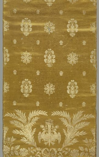 Pale yellow satin with fairly wide set vertical/horizontal repeat of twilled white silk rosettes alternating with anthemion-like forms of leaves radiating from a cone. Small, stylized flower forms fill spaces between these elements. As base of panel in twilled tan and white silk are flambeau flanked with doves addorsed regardant holding rose bud in their beaks and framed with two branches of laurel caught at the bottom with a flowing ribbon bow knot. On either side, partial repeat of flambeau grouped with feathered arrow ends and roses. Two striped satin selvages. Made in: France. Date: 1810s. Record ID: chndm_1951-9-1.