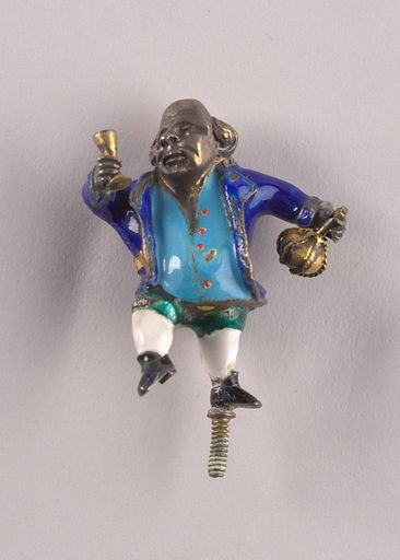 Enameled and gilt metal figurine of bald-pated man holding brass decanter and wine glass. Enameled costume: royal blue jacket with tan belt, blue waistcoat with red buttons, green breeches, white stockings, black shoes. Threaded pin for support on base of left foot. Made in: Vienna, Austria. Date: 1900s. Record ID: chndm_1952-164-17.