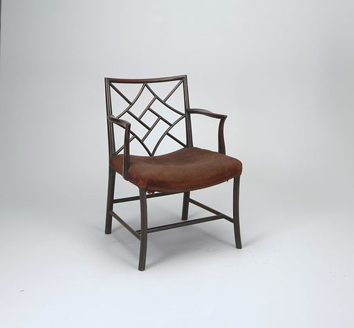 """A side chair with a rectangular back filled with a lattice-work of curved members. Its curved arms are supported on shaped stumps secured to side rails. Round rear legs; """"cluster"""" front legs. Two lateral and two longitudinal stretchers. Hollowed seat upholstered in brown wool. Described as """"cockpen"""" armchairs. Made in: England. Date: 1770s. Record ID: chndm_1900-25-14."""