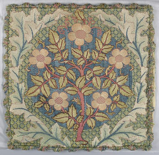 Design of flowering rose stem surrounded by wreath of oak leaves. Finished on all four sides with fringe in colors used in the embroidery. Made in: England. Date: 1890s. Record ID: chndm_1944-71-6.