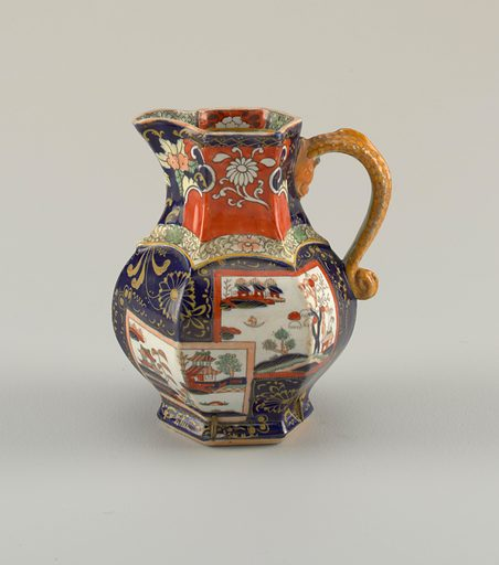Hexagonal in plan; pear-shaped with flaring foot and open spout. Handle in form of dragon. Imari style polychrome overglaze decoration: on blue ground flowers and reserve landscape vignettes. Made in: Staffordshire, England. Date: 1820s. Record ID: chndm_1953-17-130.