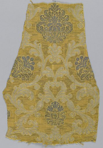 Gold-colored silk ground with extra weft of flat silver strips. Symmetrical design of swinging acanthus branches enclosing palmettes which are brocaded in silver thread. White silk extra weft appears in acanthus foliage areas. Made in: Italy. Date: 1500s. Record ID: chndm_1896-1-118.