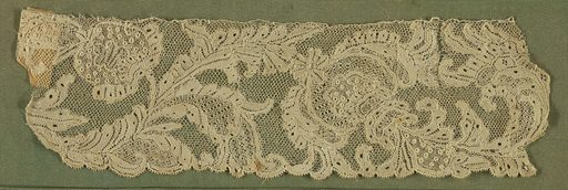 Border fragment with an elaborate conventionalized serpentine floral design. Many minute rosettes in relief. Many openwork stitches in the design. Small scallops on the the border. Made in: France. Date: 1740s. Record ID: chndm_1897-8-262.