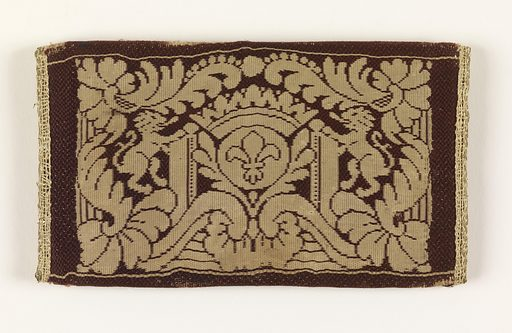 Small flat envelope-shaped case, probably for letters. Dark red silk, basket weave, with woven design in cream color. Back has woven design of a fleur-de-lis on an orb with crown above, and flanked by two lions rampant. Flap, symmetrical foliage decoration. Clasp is lyre-shaped in silver. Blue silk lining. Same pattern on both sides. Made in: France. Date: 1700s. Record ID: chndm_1951-105-14.