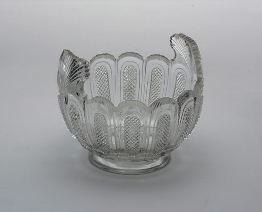 Round body on short foot, 2 fan-shaped handles extending up from scalloped lip; body cut with design of vertical sections each with an oval panel of small diamonds, thin vertical fluting sections around lip, rayed flutes on handles; cutting very sharp. Made in: Ireland. Date: 1800s. Record ID: chndm_1986-61-168.