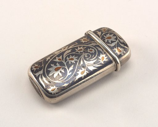 Oblong, with rounded sides and corners, featuring silver, winding, flowered tendrils attached to larger, central, paisley motif, center of flower forms punctuated with copper, all on darker steely-gray ground; reverse features same decoration. Lid, hinged on side, has protruding, rounded lip running along its lower edge; initials, possibly YM, engraved on lid top. Small, oval shaped striker on bottom. Made in: New York, New York, USA. Date: 1890s. Record ID: chndm_1982-23-56.