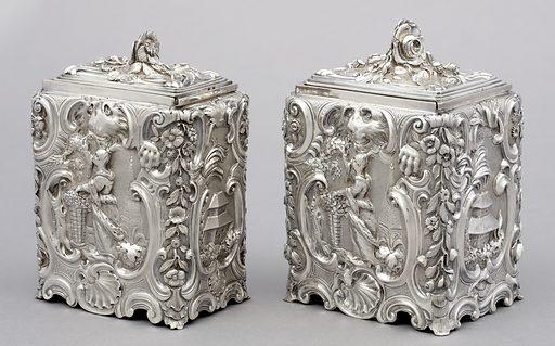 Each caddy (a,b and c,d) formed of upright, rectangular body with repousse decoration of tea-picking chinoiserie figures in scrolled cartouche, with lion's head above and shell below, on front and back. On sides, scene of building and foliage in scrolled cartouche. Each caddy with sliding cover, relief-cast, with flower knob. Made in: London, England. Date: 1750s. Record ID: chndm_1960-1-1-a_d.