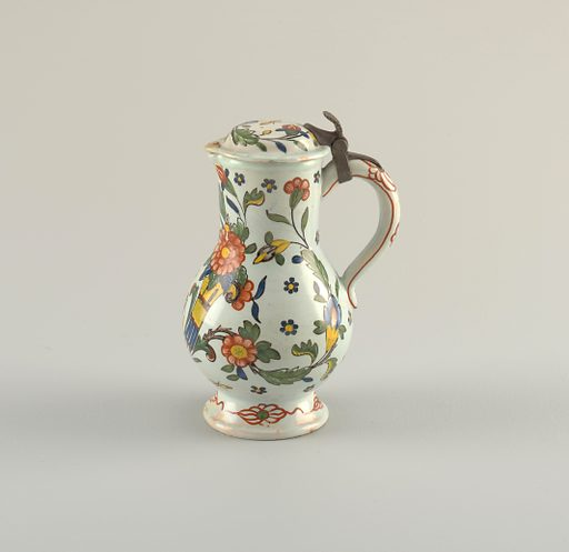 Pyriform jug of pinkish buff paste with greenish glaze. Rounded loop handle; slightly domed cover, covering spout, hinged to handle by pewter hinge. Horn-of-plenty and flowers in blue, green, yellow and iron red, outlined in black. Made in: Sinceny or Rouen, France. Date: 1720s. Record ID: chndm_1958-119-5.