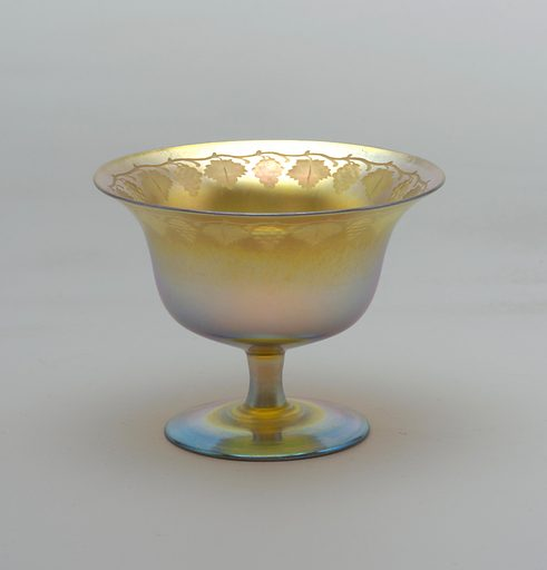 Spreading foot and short plain stem support bowl flaring to lip – iridescent – engraved band of symmetrical vintage mofits about inside upper margin. Designer: Louis Comfort Tiffany, American, 1848–1933. Made in: USA. Date: 1910s. Record ID: chndm_1948-64-63.