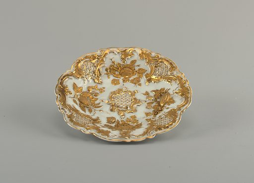 Oval plate with scalloped edges, partially gilded with floral relief ornament. Date: 1820s. Record ID: chndm_1959-155-12.
