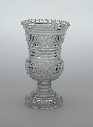 Baluster shaped, with flaring rim and scalloped lip; short knopped stem, high stepped base; cut in strawberry diamond pattern all over with prismatic rings under lip, middle of sides and top of base; glass very reflective. Date: 1820s. Record ID: chndm_1986-61-86.