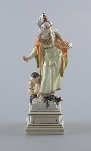 """""""Asia"""" standing female figure, wearing turban and holding pieces of cinnamon and an elephant tusk; attended by seated, turbaned putto, holding censer and horse-tail sceptre; square pedestal. Date: 1770s. Record ID: chndm_1960-1-44-a."""
