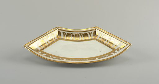 White, with stylized palmettes in gilt. A) circular bowl, the flaring rim with vine motif. B) low cover with knob handle, rests inside rim bowl. C to F are curved to form a circle around the bowl. Date: 1810s. Record ID: chndm_1926-22-506-c.