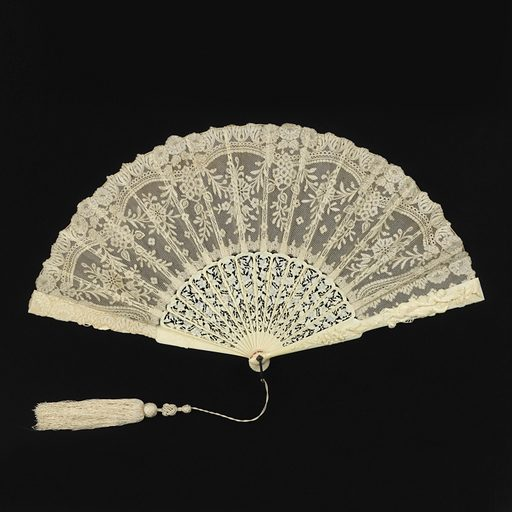 Pleated fan. Leaf ofwhite cotton bobbin-made Valenciennes lace in floral design, backed with silk net. Sticks of pierced and carved ivory in floral design. Guards with figures of birds, cupids and insects. Metal loop at the rivet. Attached tassel. Made in: France. Date: 1880s. Record ID: chndm_1942-34-9-a.