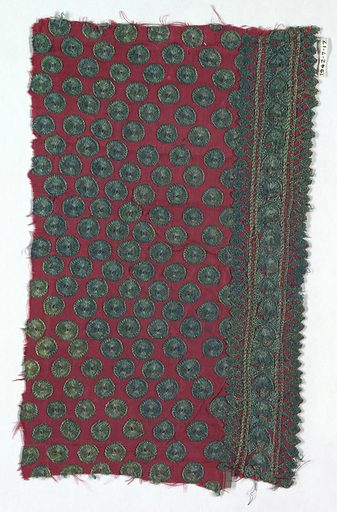 Fragment of a child's tunic with a ground of red silk decorated with green discs and a border at one side of semi-circles and ovals placed in a lattice format with connecting chevrons. Made in: India. Date: 1800s. Record ID: chndm_1942-7-17.
