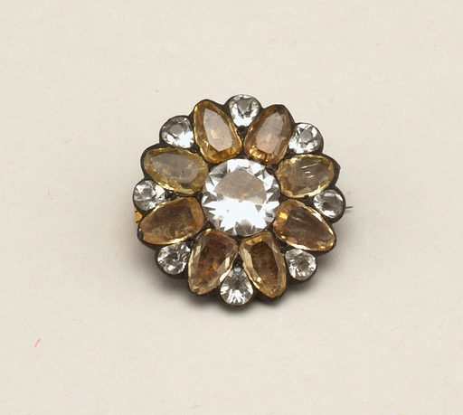 Brooch in the form of a flower with a white center, eight yellow petals and a small white stone set between each two petals. Pin is a replacement. Made in: France. Date: 1800s. Record ID: chndm_1943-47-2.