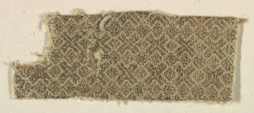 Small fragment of coarse material, said to have come from an abbey in France. Lozenge pattern formed by the manner in which twill is tied down. Warps are natural unbleached fibers, and wefts are coarsely spun. Made in: Europe. Date: 1200s. Record ID: chndm_1943-52-3.