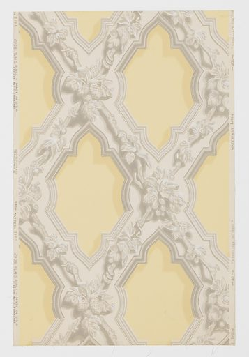 """Representing ornamental plaster form of decoration in English Gothic used in the first half of the 19th century. Composed of criss-crossing wide bands ornamented with leaves, flowers, nuts and fruits. Bands are edged with simulated moldings. A reproduction of an old wallpaper from the walls of the front entry of John Sible's house, Hancock Street, Salem, Massachusetts. It was put on walls in 1858. Printed on reverse side: """"No. 295 CB"""". Printed in grisaille on pale gold field. Not original colors. Made in: Buffalo, New York, USA. Date: 1920s. Record ID: chndm_1945-12-27."""