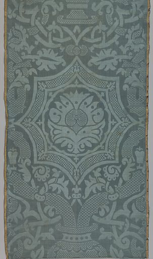 Gray-blue damask with large symmetrical design of a vase with two heavy stems framing a curved octagon with a stylized palmette inside. Highly stylized vine and leaf pattern with elaborate interlacing. Vase, vine and branches filled with a diaper pattern. Broad satin selvages striped in salmon and yellow. Made in: Spain. Date: 1630s. Record ID: chndm_1955-34-1.