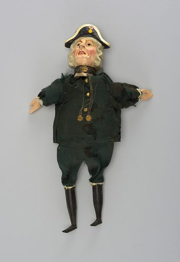 Brightly painted head with black and white bicorn with tri colored cockade. Green uniform. Black hose and shoes. Gold buttons and decorations. Lace at knees and cuffs. Possible a caricature of Admiral Nelson. Made in: England. Date: 1900s. Record ID: chndm_1950-58-11.