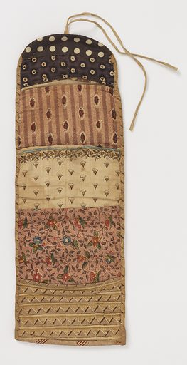 Folding oblong needle case made of seven different printed cottons; four pockets, one with a piece of wool for needles. In one pocket a small semicircle of newspaper dated 1838. Made in: USA. Date: 1830s. Record ID: chndm_1951-108-4.