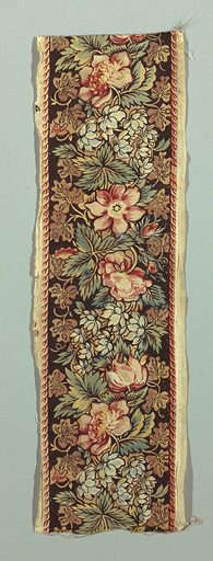 """Narrow band with a dark brown ground showing tightly clustered flowers and leaves in red, light brown, blue, yellow, and """"double green"""" (blue printed with yellow). Border on both edges showing a row of small red wishbone shapes. Made in: England. Date: 1810s. Record ID: chndm_1952-105-11."""