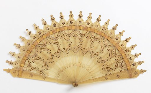 Brisé fan. Blond horn decorated on obverse with gold painting of floral, fern, wheat and feather motifs. Sticks connected by gold-colored ribbon. Steel piqués arranged in scalloped band below ribbon. Made in: France. Date: 1820s. Record ID: chndm_1952-161-209.