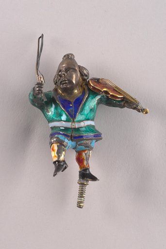 Metal figurine of bald-pated man with top knot holding bow and brown enamel violin with gold strings and edging. Enameled costume: green jacket with gray blet, royal blue waistcoat with gold buttons, light blue breeches, white stockings with red and yellow mottling, black shoes. Threaded pin on base of left foot. Traces of gilding on neck, throat and violin bow. Made in: Vienna, Austria. Date: 1900s. Record ID: chndm_1952-164-18.