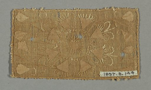 Light brown rectangular fragment with a crude floral form suggested by a spoked circle surrounded by triangular petals. Left and right edges have diamond shapes connected by lines of stitching. Made in: Belgium or France. Date: 1600s. Record ID: chndm_1897-8-144.