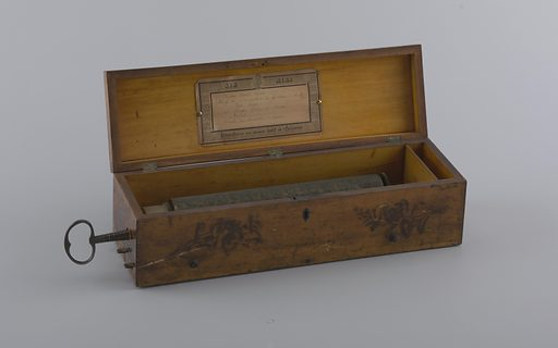 Wood box with lid attached with three hinges. At front, decoration of two roses, and a keyhole. At side, a key with the mark: IP. IG. Inside is the music cylinder. Printed paper label affixed inside the lid with two brass tacks. Striped border with lyre and face. Text reads: Six Airs / Etouffoirs en acier soit a Spiraux. Listed at center are the songs: Home Sweet Home; Motif de l'Ouverture de Gustave, d'Auber; Jim Crow; Berger Galop de Strauss; Isabel; and Finale du Serment, d'Auber. Made in: Switzerland. Date: 1900s. Record ID: chndm_1957-165-1-a_b.