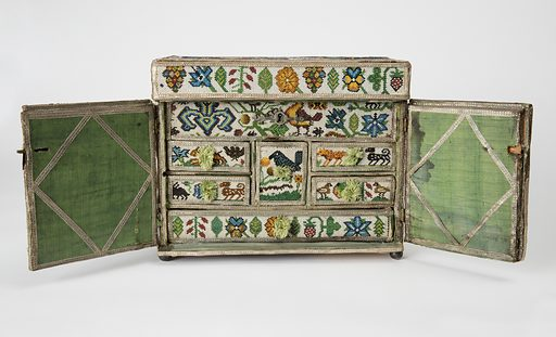A beaded casket with a hinged top and two doors which open to show a series of small drawers. The wooden frame is covered with white satin and beaded with many colors of glass beads, strung on linen thread in a simple looping structure. The doors are lined with green silk and the whole is trimmed with silver braid. The arms of Basnet appear on the left door and the arms of Dand on the right. On the top is a scene of four figures visiting a royal personage, and the remainder is covered with flowers and birds. Made in: Coventry, England. Date: 1650s. Record ID: chndm_1947-70-1.