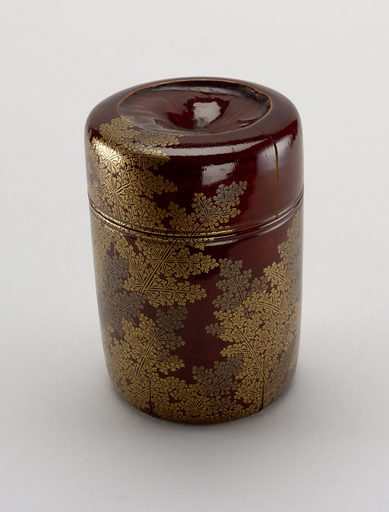 Cylindrical box with cover, made of a segment of a bamboo stem. Ferns in gold 'hira-makiye' lacquer on ground of 'shunkei-nuri' (reddish-brown) lacquer. The depressions in top and underneath are due to formation of the node of the bamboo segment. The ferm is a symbol associated with Japanese New Year's ceremonies. Made in: Japan. Date: 1800s. Record ID: chndm_1952-164-13-a_b.