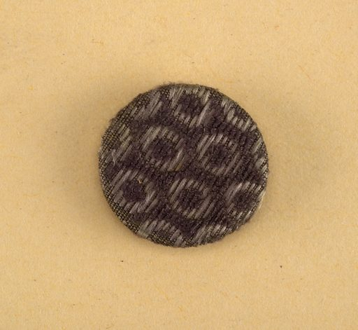 From originally a set of seventeen buttons, of three different sizes, to go with the man's suit of which 1939-57-30-a to c are parts – bone shapes covered with purple velvet uncut pile which forms minute hexagons each enclosing a round dot against a ground with short floats of secondary purple silk weft. Date: 1790s. Record ID: chndm_1939-57-29-e.