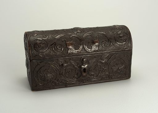 Casket-shaped box, fitted with iron lock, made of tooled leather over wood; surface design showing Renaissance style masks, and foliated scrolls with bird-like animals, decorated with large curves. Inside lining of brown silk taffeta with embroidery in green and brown silk showing trees, leaves, and architecture. Made in: Italy. Date: 1500s. Record ID: chndm_1947-16-4-a.