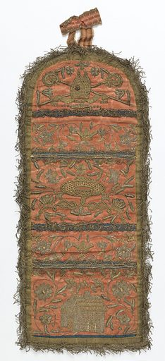 Wall pocket with two pockets and a rounded top. Made from coral-colored silk taffeta, embroidered in gold and silver threads. The lower pocket has a house surrounded by flowering vines. The upper pocket shows a cardinal's hat with flowering vines. At the top, a bishop's mitre with a red stone inset, and crossed croziers. Trimmed with gold fringe and gold lace. Pockets lined with blue silk. Backed with leather. Made in: Germany, Austria, or Switzerland. Date: 1800s. Record ID: chndm_1950-121-50.