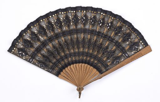 Pleated fan. Metallic net leaf backed with black chiffon. Obverse: decorated with bands and diamonds of black sequins and paillettes sewn on taffeta as well as metal net. Carved sandalwood and pierced sticks. Made in: possibly USA. Date: 1900s. Record ID: chndm_1951-106-2.