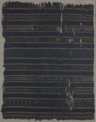 Dark blue silk cloth crossed at half inch intervals by bands of geometric repeats with guard bands above and below formed by pale yellow, pale blue and black wefts. One plain selvage, at right angles to bands, terminating in pale yellow silk cord. Made in: Egypt. Date: 1100s. Record ID: chndm_1951-111-36.