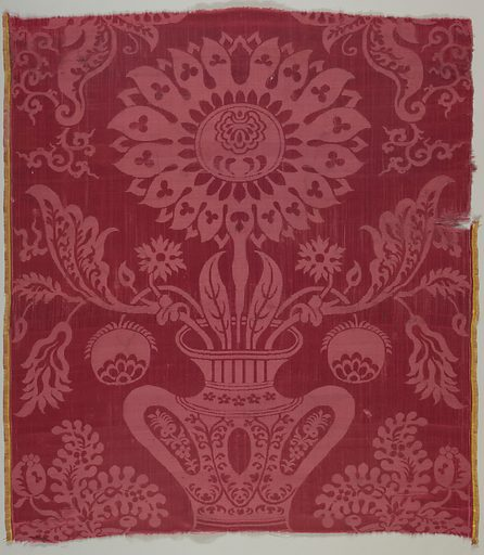 Red damask with a symmetrical arrangement of a large flower coming from a vase. Made in: China. Date: 1700s. Record ID: chndm_1902-1-914.