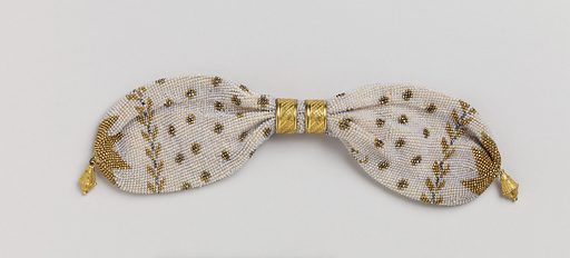 """Initialed """"AC"""" and """"JC""""; a base of cream-colored knitted silk is solidly covered with minute opalescent beads; it is further ornamented with gold and cut steel beads in a stylized leaf pattern and a pattern of small rosettes. Two gold rings control side opening; small gold drops at either end. Made in: France. Date: 1810s. Record ID: chndm_1953-106-94."""