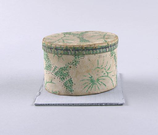 Very small oval-shaped bandbox. Paper is probably wallpaper: chalky-white flowers and leaves picked out in bright green. Small black dots are sprinkled over a portion of the design. The cover is edged with a fluted design, shaded with dark gray. Date: 1800s. Record ID: chndm_1948-32-1-a_b.