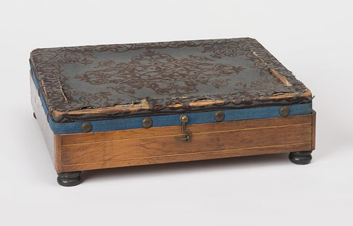 Rectangular wooden stool (a) on bun feet, with hinged lid covered in blue printed wool, mounted with upholstery nails; Rectangular tin liner (b) in stool. Date: 1880s. Record ID: chndm_1956-42-87-a_b.
