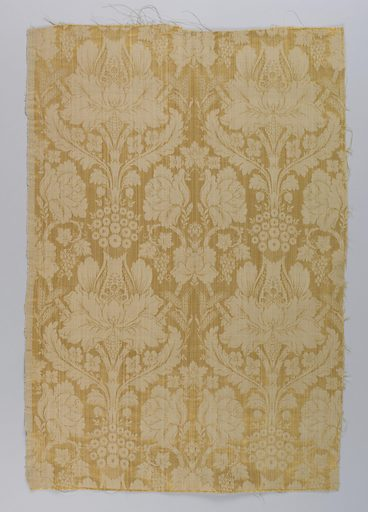 Upholstery fabric of unbleached linen woven with gold silk in a design of formalized flowers and leaves arranged in vertical stripes. Made in: USA. Date: 1880s. Record ID: chndm_1941-53-4.