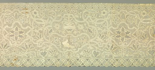 Oblong panel of very fine linen with elaborate design in fine drawn work in which the main lines of the design are reserved in linen. The background, centers of flowers and other small details are rendered in a variety of drawn thread patterns. In center, an urn with flower sprays and vines symmetrically arranged. Below is a bird, and at right and left, a symmetrical arrangement of curving vines and flowers of natural size. Lower edge is scalloped. Birds and other details are embroidered in white. Made in: France. Date: 1800s. Record ID: chndm_1952-162-118.