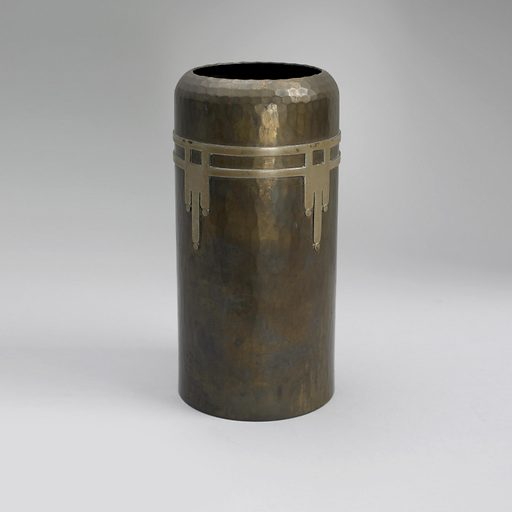 Hammered cylindrical vase gently narrowing at the top with a simple decoration of German silver in a Native American pattern, a double band encircling the vase with a dropping design at four points. Made in: East Aurora, New York, USA. Date: 1910s. Record ID: chndm_2013-21-41.