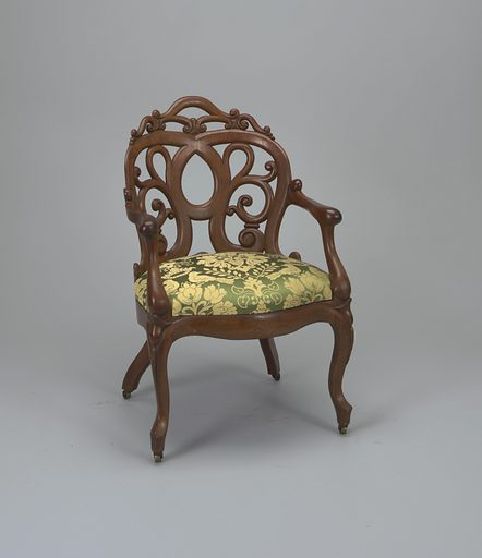 Armchair with shaped openwork back, curved in plan; serpentine arms join back to scrolled front of seat; cabriole front legs, curved and splayed rear legs, all fitted with castors. Seat upholstered in green and cream colored fabric. Made in: New York, New York, USA. Date: 1860s. Record ID: chndm_1971-8-1-a.