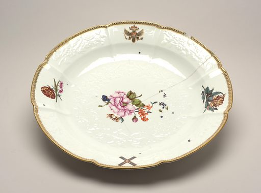 Circular form, with overglaze gilt and red border and Russian Imperial arms opposite the Imperial Order of St Andrew the first called, on the rim, the central well with underglaze moulded white floral pattern, and colorful Deutsche Blumen scattered over the whole surface. Date: 1740s. Record ID: chndm_1923-22-51.