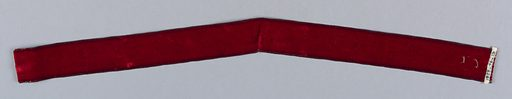 Red velvet ribbon, shaped into a curve with stitches at center. Made in: USA. Date: 1900s. Record ID: chndm_1923-46-19.