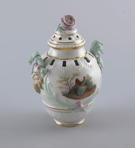 Potpourri vase molded with relief decoration around piercings on shoulder and lid. Gilded bands at base, neck and lid. Handles with mascarpone crowned with water reeds. Painted courtship scenes. Knob in the form of a rose. Date: 1830s. Record ID: chndm_1938-57-377-a_b.
